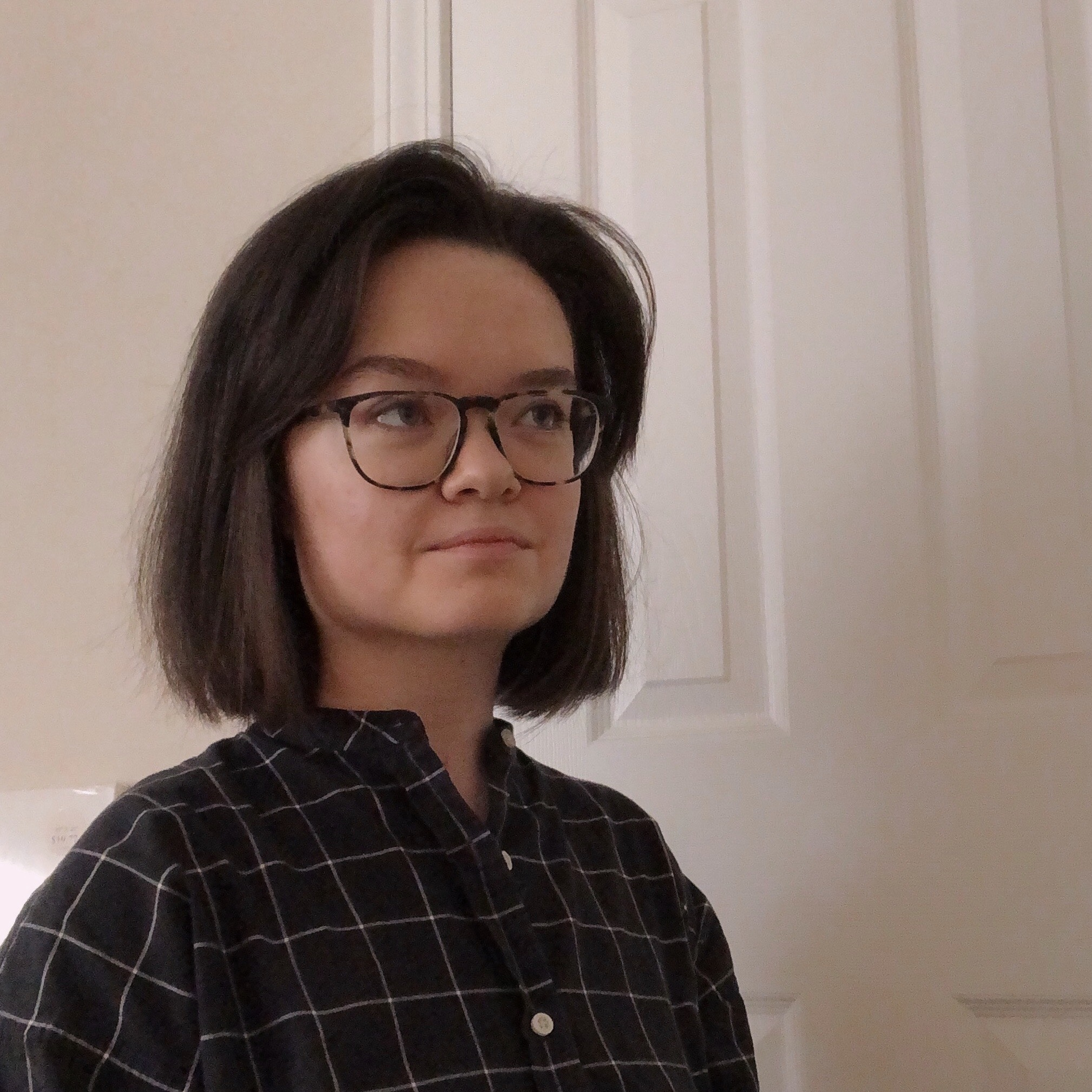 Photo of Anna Grace Sherlock. She's a white woman with shoulder-length brown hair and glasses. She's wearing a black and white checked shirt and is looking up and to the side, optimistic.